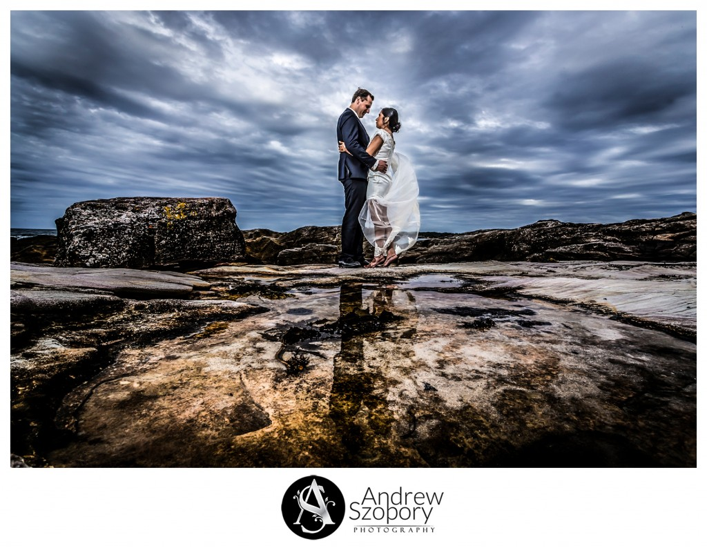 wedding photo taken by the side of a rock pool at Oak Park cronulla on a an overcast day. Bride and groom stair lovingly into each others eyes.