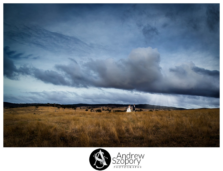 Bride and groom walk across large open rolling hills inear Cullerin nsw at the Old Coach Stables Restaurant