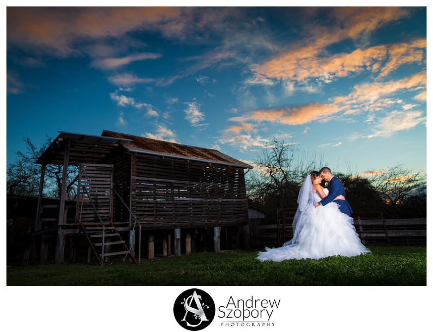 bride and groom stand outside near sheep shearing shed at Belgenny farm and hug during sunset