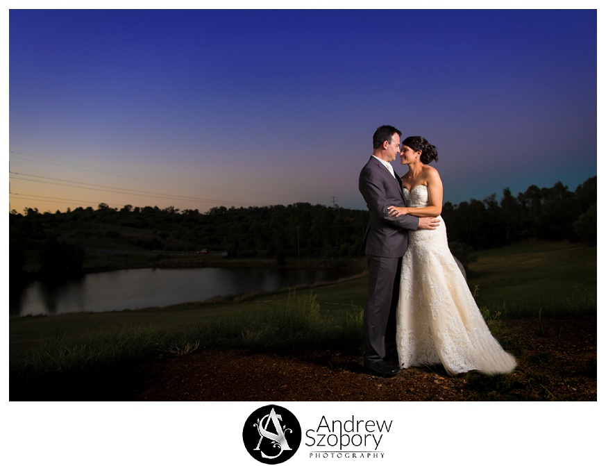 Bride and groom hug on hill overlooking macarthur grange golf club
