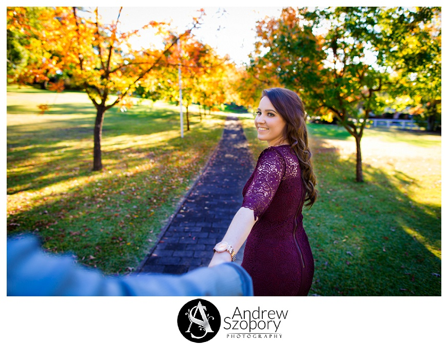 pre wedding bride to be leads groom through tree lined path in autumn