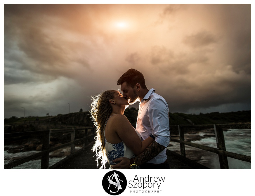 bride and groom kiss during stormy afternoon