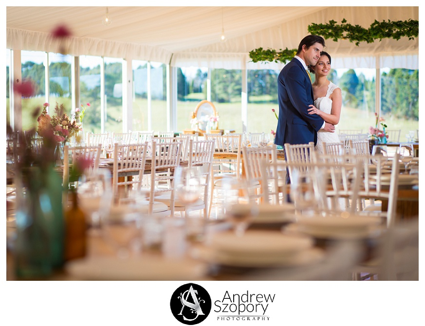 couple standing in grand marquee with rustic styling